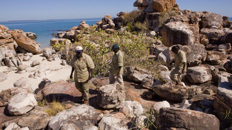 Three Indigenous rangers walking across rocks near the ocean